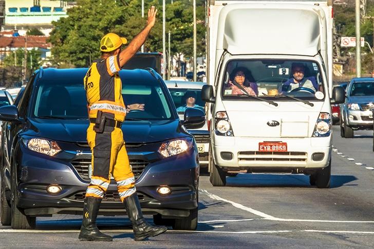 Guarda de trânsito orientando motoristas.