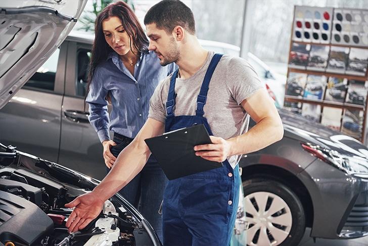Mecânico e cliente analisando motor do veículo