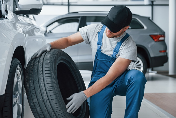 Mecânico trocando pneu do carro